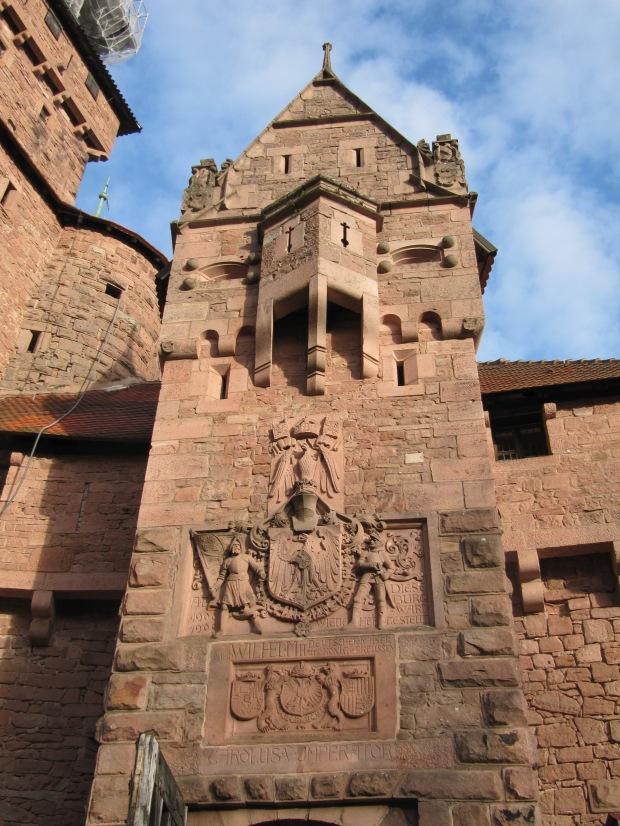 Le château est en grès rose des Vosges, et ça se voit. Le tout est magnifique. La porte d'entrée vante les mérites du restaurateur, Guillaume II.